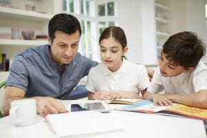 father helping son and daughter with homework