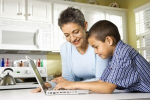 woman and young boy looking at computer